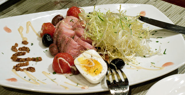 Big Eye Tuna Nicoise - Olive oil poach tuna, with assorted olives, capers, hard-boiled egg, frisee, cinfit campari tomatoes, raw honey emulsion, fried bread & red wine vinegar syrup.